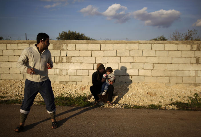 In this Friday, Dec. 14, 2012, photo, a Syrian rebel holds his friend's daughter while sitting on a roadside in Maaret Misreen, near Idlib, Syria. The town is broke, relying on a slowing trickle of local donations. The rebels, a motley crew of laborers, mechanics and shopowners, have little experience in government. President Bashar Assad's troops still control the city of Idlib a few miles away, making area roads unsafe and keeping Maaret Misreen cut off from most of Syria. (AP Photo/Muhammed Muheisen)