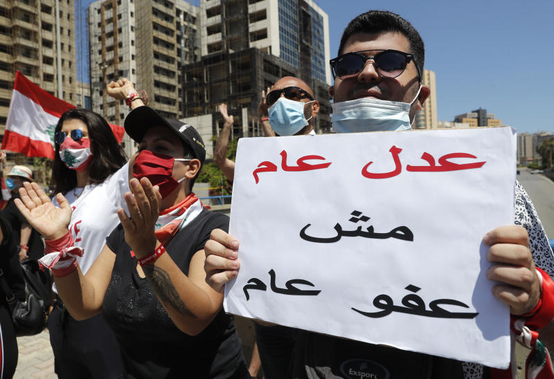 """Anti-government protesters cover their faces with masks to help curb the spread of the coronavirus during a protest against a general amnesty law being proposed in parliament, in Beirut, Lebanon, Thursday, May 28, 2020. The Arabic placard reads, """"General justice and not a general amnesty."""" (AP Photo/Hussein Malla)"""