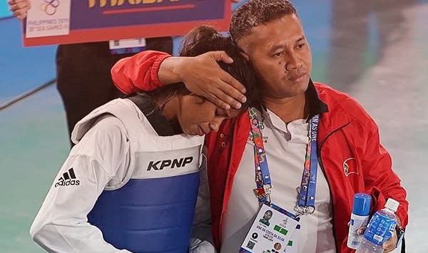 Timor Leste taekwondo athlete Ana Da Costa had to be consoled by her coach after losing her final and the opportunity to win gold. (PHOTO: Facebook)