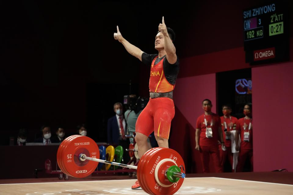 Shi Zhiyong of China celebrates after winning the gold medal in the men's 73kg weightlifting event, at the 2020 Summer Olympics, Wednesday, July 28, 2021, in Tokyo, Japan. (AP Photo/Luca Bruno)