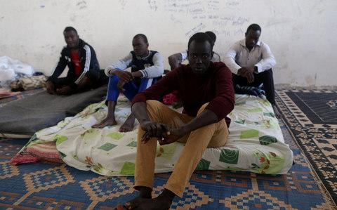 Migrants sit in a detention centre run by the interior ministry of Libya's eastern-based government, in Benghazi - Credit: Reuters