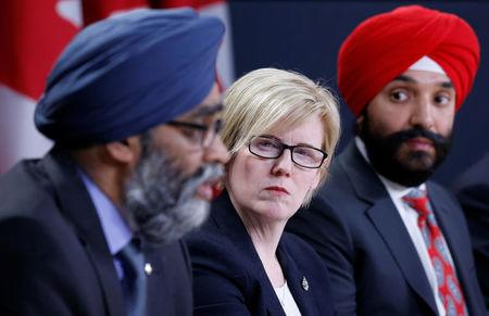 Canada's Public Works Minister Carla Qualtrough (C) and Innovation Minister Navdeep Bains (R) listen to Defence Minister Harjit Sajjan speak during a news conference in Ottawa, Ontario, Canada, December 12, 2017. REUTERS/Chris Wattie