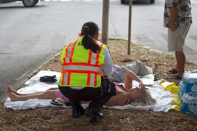 <p>A paramedic checks on a woman, lying on a median, after she and others exited the Marco Polo apartment complex as firefighters continue to battle a blaze at the high-rise, Friday, July 14, 2017, in Honolulu, Hawaii. (Photo: Marco Garcia/AP) </p>