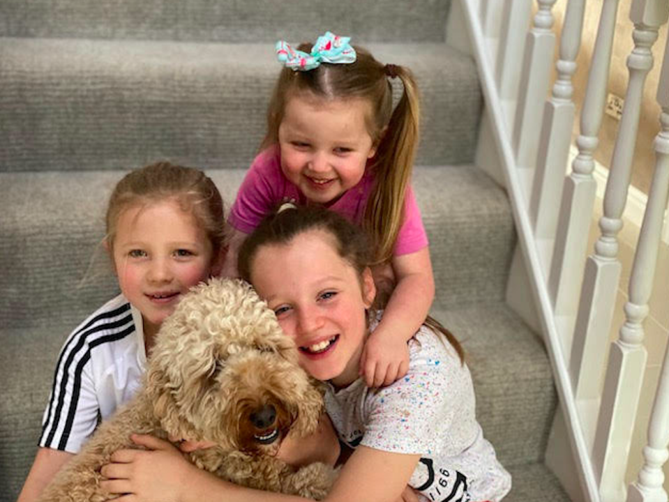 Benji the dog with (L-R) Scarlett Malley, Seren Malley (back) and Sienna Malley. (SWNS)