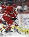 Carolina Hurricanes' Jiri Tlusty (19), of the Czech Republic, and Calgary Flames' Ladislav Smid (15), of the Czech Republic, chase the puck during the second period of an NHL hockey game in Raleigh, N.C., Monday, Nov. 10, 2014. (AP Photo/Gerry Broome)