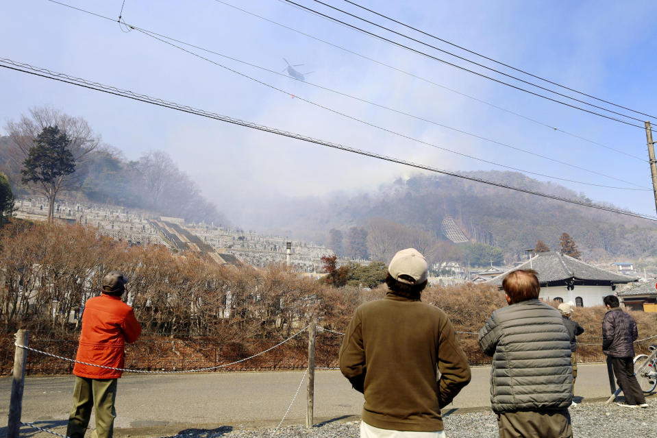 Residents watch as a helicopter dumps water on a wildfire in Ashikaga, Tochigi prefecture, north of Tokyo Wednesday, Feb. 24, 2021. A forest fire broke out in the rural area Thursday, near another blaze burning since Sunday, Feb. 21. (Kyodo News via AP)