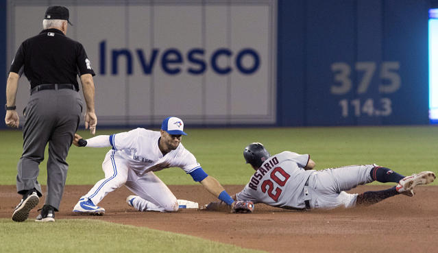 Minnesota Twins' Eddie Rossario safe stealing second base as Toronto Blue Jays' Lourdes Gurriel Jr. misses with the tag attempt in the eighth inning of their baseball game in Toronto on Tuesday, July 24, 2018. (Fred Thornhill/The Canadian Press via AP)