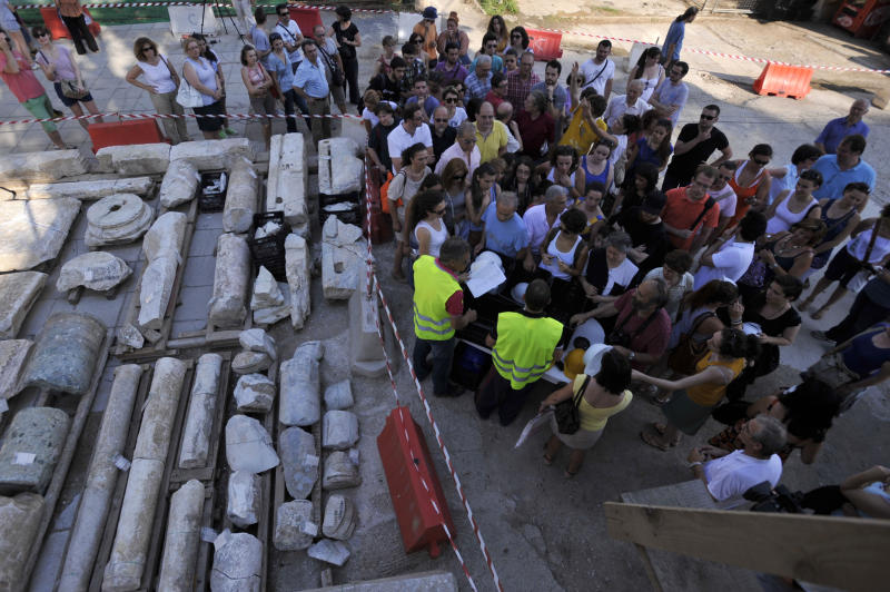 Archaeologists and employees of Metro's construction company present to the media and public the ancient ruins in the northern Greek port city of Thessaloniki on Monday, June 25, 2012. Archaeologists in Greece's second largest city have uncovered a 70-meter (230-foot) section of an ancient road built by the Romans that was city's main travel artery nearly 2,000 years ago. The marble-paved road was unearthed during excavations for the city's new subway system that is due to be completed in four years, and will be raised to be put on permanent display for passengers when the metro opens. (AP Photo/Nikolas Giakoumidis)