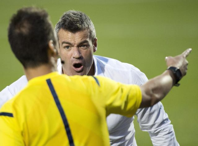 Toronto FC head coach Ryan Nelsen, right, argues a call with one of the officials while playing against Sporting Kansas City during second-half MLS soccer game action in Toronto, Saturday, July 26, 2014. (AP Photo/The Canadian Press, Nathan Denette)