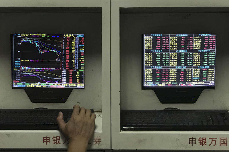 A man monitors stock prices at a brokerage house in Beijing, Monday, July 16, 2018. Shares edged lower in Asia early Monday after China reported lackluster growth data in line with expectations. (AP Photo/Andy Wong)
