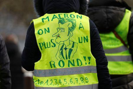 "A protester wearing a yellow vest attends a demonstration with French unions against the French government policies in front of the sport hall ""La Maison du Handball"" during a visit of French President Emmanuel Macron in Creteil near Paris, France, January 9, 2019. The slogan reads ""Macron we're broke"". REUTERS/Charles Platiau"