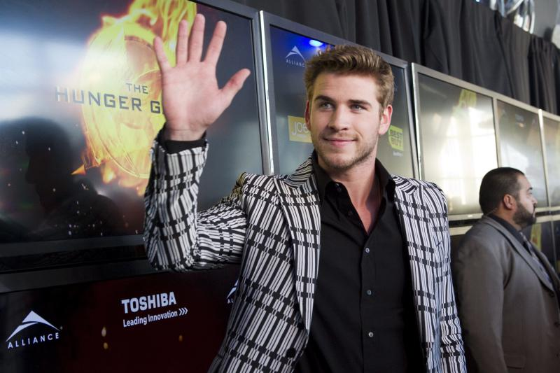 """Liam Hemsworth, who portrays Gale Hawthorne, waves to fans as he arrives on the red carpet for the premier the film """"The Hunger Games"""" on Monday March 19, 2012 in Toronto. (AP Photo/The Canadian Press, Chris Young)"""