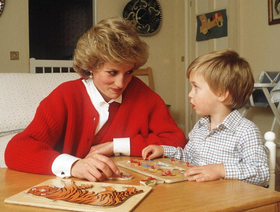 <p>Sweaters were a key piece of Diana's mom wardrobe, like this red cardigan she wore while doing a puzzle at home with William.</p>