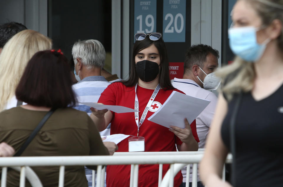A Red Cross volunteer hands people papers before entering the COVID-19 vaccination center, at A1 Arena in Skopje, North Macedonia, on Tuesday, May 4, 2021. The European Union started delivering EU-funded coronavirus vaccines Tuesday to the Balkans, a region that wants to join the 27-nation bloc but where China and Russia have already been supplying the much-needed shots and making political gains. (AP Photo/Boris Grdanoski)
