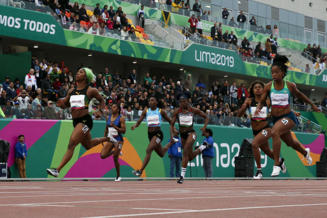 Shelly-Ann Fraser-Pryce ofJamaica, left, wins the gold medal and sets a new Pan American record in the women's 200m final during the athletics at the Pan American Games in Lima, Peru, Friday, Aug. 9, 2019. (AP Photo/Moises Castillo)