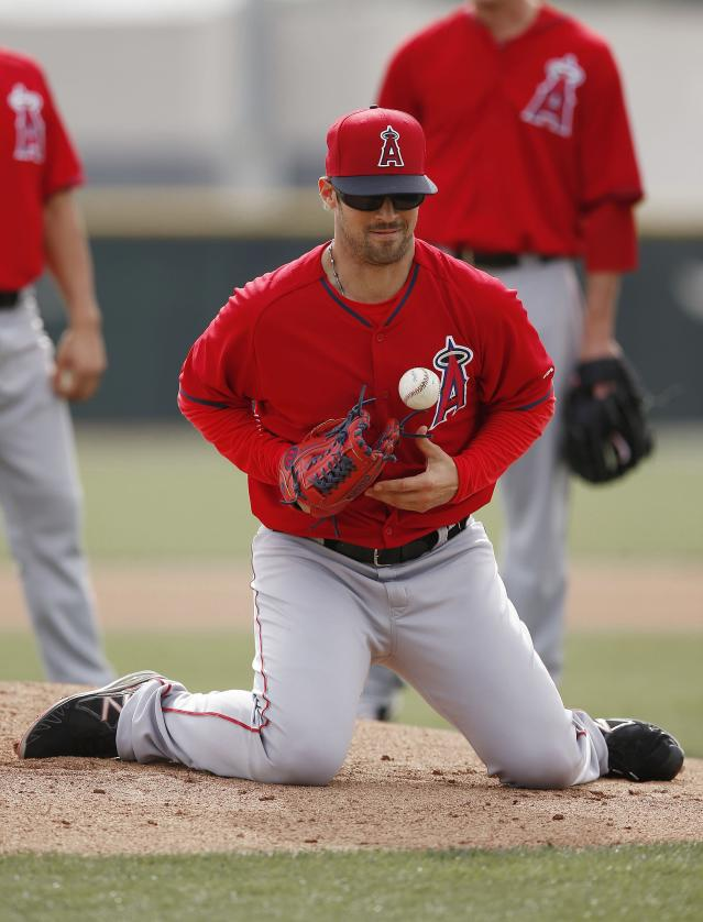 Los Angeles Angels' C.J. Wilson squats on the ground as he stops a ground ball during pitcher fielding drills during spring training baseball practice on Tuesday, Feb. 25, 2014, in Tempe, Ariz. (AP Photo/Ross D. Franklin)