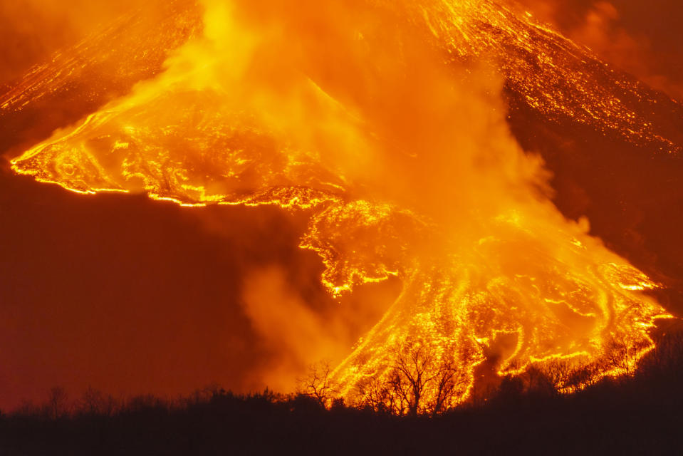 A fiery river of glowing lava flows on the north-east side of the Mt Etna volcano near Milo, Sicily, Wednesday night, Feb. 24, 2021. Europe's most active volcano has been steadily erupting since last week, belching smoke, ash, and fountains of red-hot lava. (AP Photo/Salvatore Allegra)
