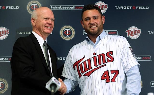 Minnesota Twins general manager Terry Ryan shakes hands with pitcher Ricky Nolasco during a press conference at Target Field in Minneapolis Tuesday, Dec. 3, 2013. The Minnesota Twins announced Tuesday they finalized a $49 million, four-year contract with right-hander Nolasco. (AP Photo/The Star Tribune, Kyndell Harkness)