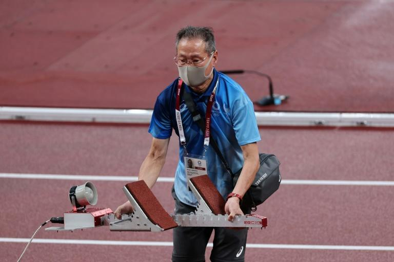 A volunteer sets up a starting block during the athletics at Tokyo 2020