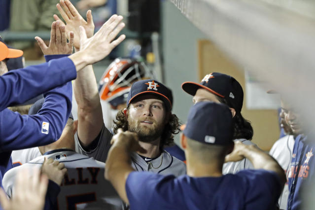 Houston Astros starting pitcher Gerrit Cole, center, is greeted in the dugout after the seventh inning of the team's baseball game against the Seattle Mariners, Tuesday, Sept. 24, 2019, in Seattle, after Cole broke the Astros' franchise record for strikeouts in a season. (AP Photo/Ted S. Warren)