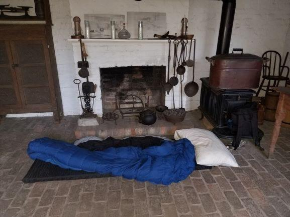 A sleeping bag is shown inside of the one of the slave quarters visited by members of Slave Dwelling Project.