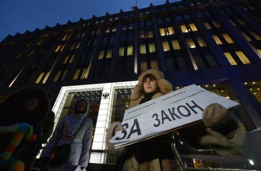 "<p>A woman holds a poster reading ""We support the bill"" outside the upper house of Russia's parliament on December 26, 2012. Russia's upper house of parliament on Wednesday unanimously backed a bill barring Americans from adopting Russian children, leaving the controversial measure in the hands of President Vladimir Putin.</p>"