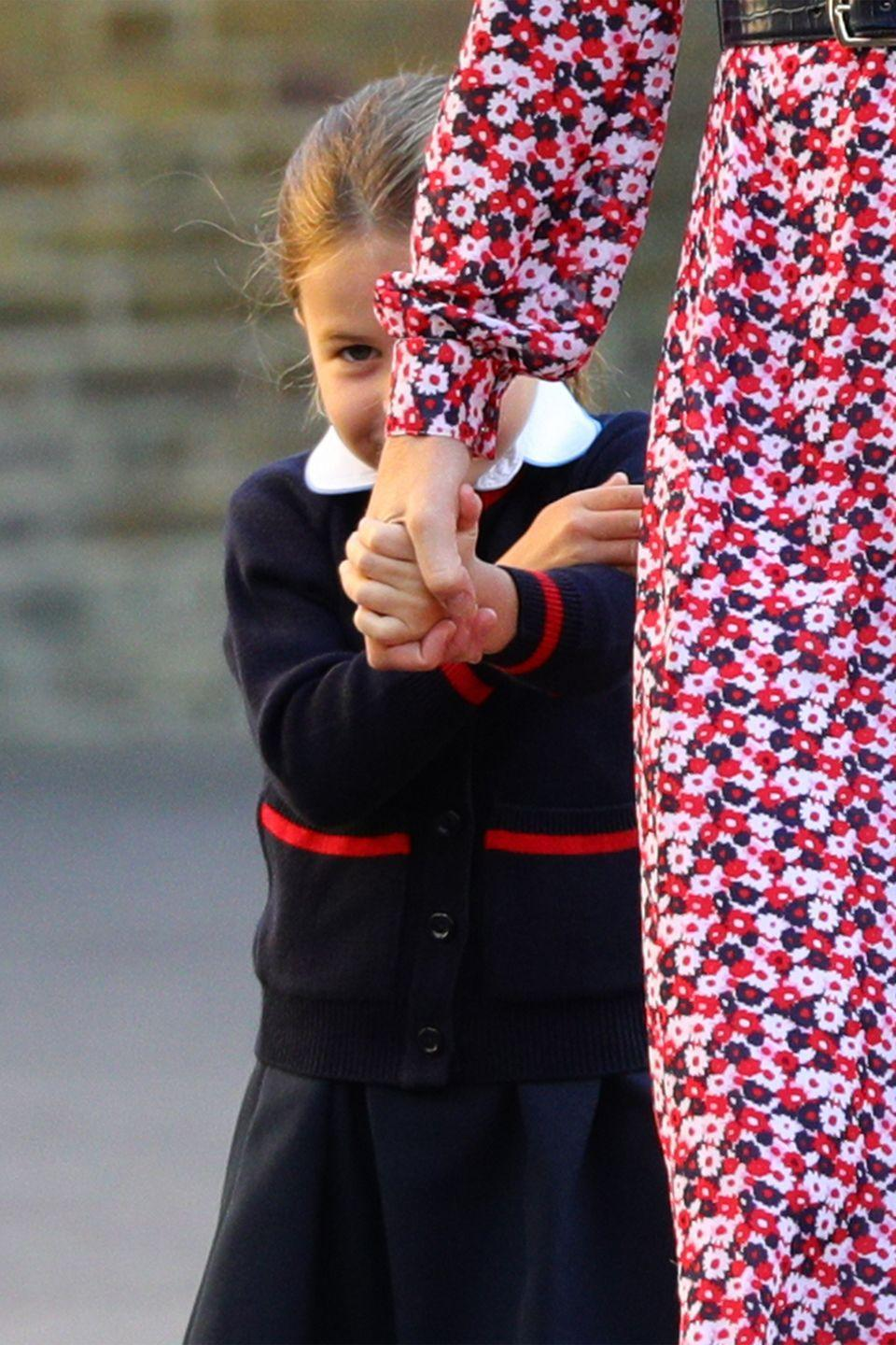 <p>Hiding behind her mother, Princess Charlotte shows a rare moment of sheepishness. </p>
