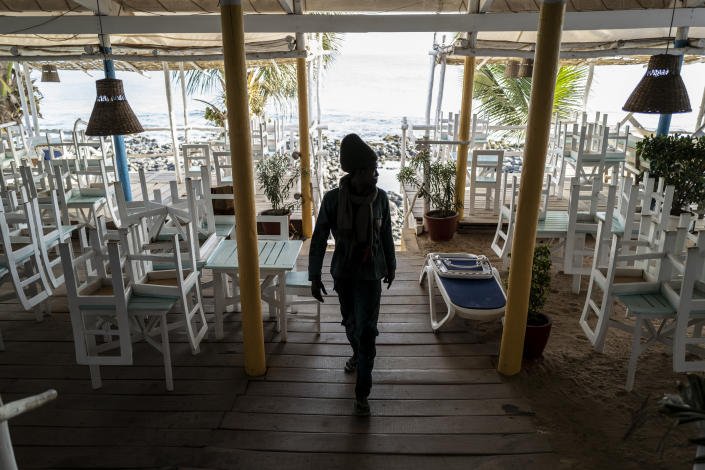 In this Thursday, March 26, 2020, photo, a security guard walks in a normally busy but now closed restaurant on a beach in Dakar, Senegal. As African countries have started shutting down borders and economic activity plummets, those who do informal work or run small businesses are suffering without the type of economic assistance that some countries in the developed world are able to provide. (AP Photo/Sylvain Cherkaoui)