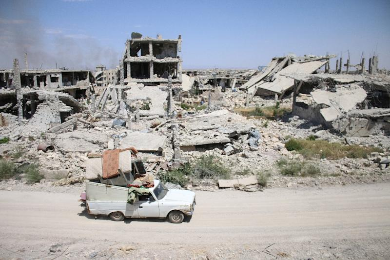 A car loaded with belongings of a displaced Syrian family drives past destroyed buildings in a rebel-held area of the southern city of Daraa on May 9, 2017 (AFP Photo/Mohamad ABAZEED)