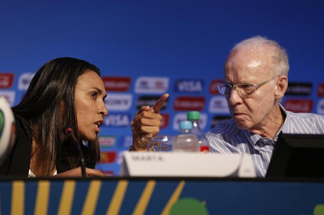 FIFA World Cup ambassadors Marta, left, and Mario Zagallo talk during a press conference in Salvador, Brazil, Thursday, Dec. 5, 2013. The draw for the 2014 World Cup soccer finals takes place Friday, Dec. 6, in Costa do Sauipe, Brazil. (AP Photo/Silvia Izquierdo)