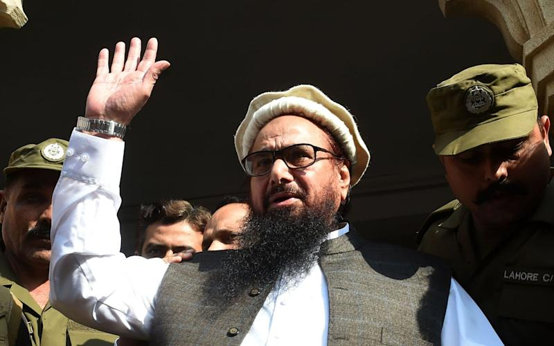 Hafiz Saeed waves to supporters as he leaves a court in Lahore on November 21, 2017. - AFP