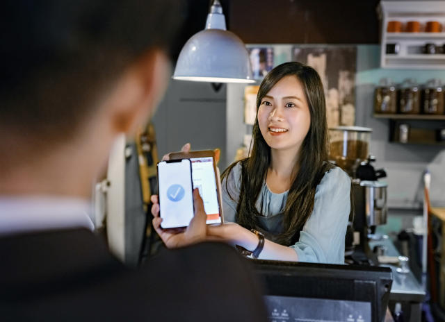 Smiling female cashier holding digital tablet at checkout. Male customer is paying through smart phone. They are at cafe.