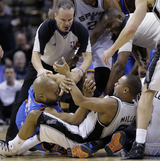 Oklahoma City Thunder's Derek Fisher, left, and San Antonio Spurs' Patty Mills, right, are pulled apart by officials during a scuffle for a loose ball in the second half of an NBA basketball game, Wednesday, Jan. 22, 2014, in San Antonio. Oklahoma City won 111-105. (AP Photo/Eric Gay)