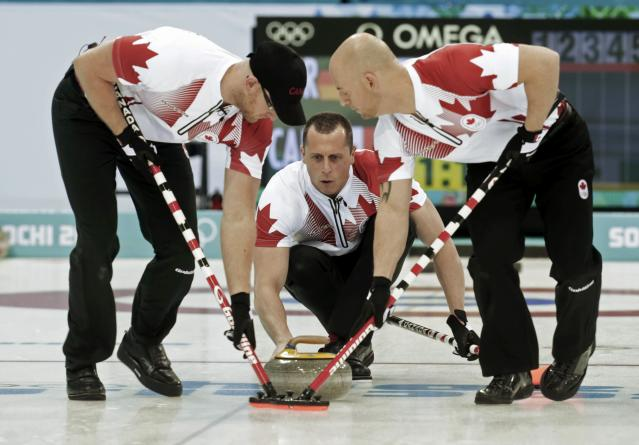 Canada's second E. J. Harnden (C) delivers a stone as vice Ryan Fry (L) and lead Ryan Harnden sweep during their men's curling round robin game against Germany at the 2014 Sochi Olympics in the Ice Cube Curling Center in Sochi February 10, 2014. REUTERS/Ints Kalnins (RUSSIA - Tags: OLYMPICS SPORT CURLING)