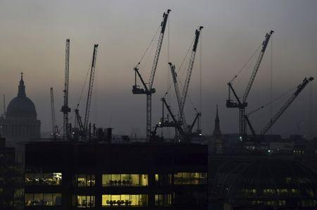 Offices are seen at dusk as St. Paul's Cathedral and construction cranes are seen on the skyline in the City of London, Britain