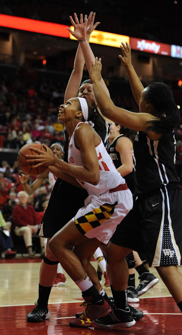 Maryland's Alicia DeVaughn, left, looks to shoot as Wake Forest's Keri Fulp (partially blocked) and Ataijah Taylor defend in the first half of an NCAA college basketball game on Thursday, Jan 9, 2014, in College Park, Md.(AP Photo/Gail Burton)