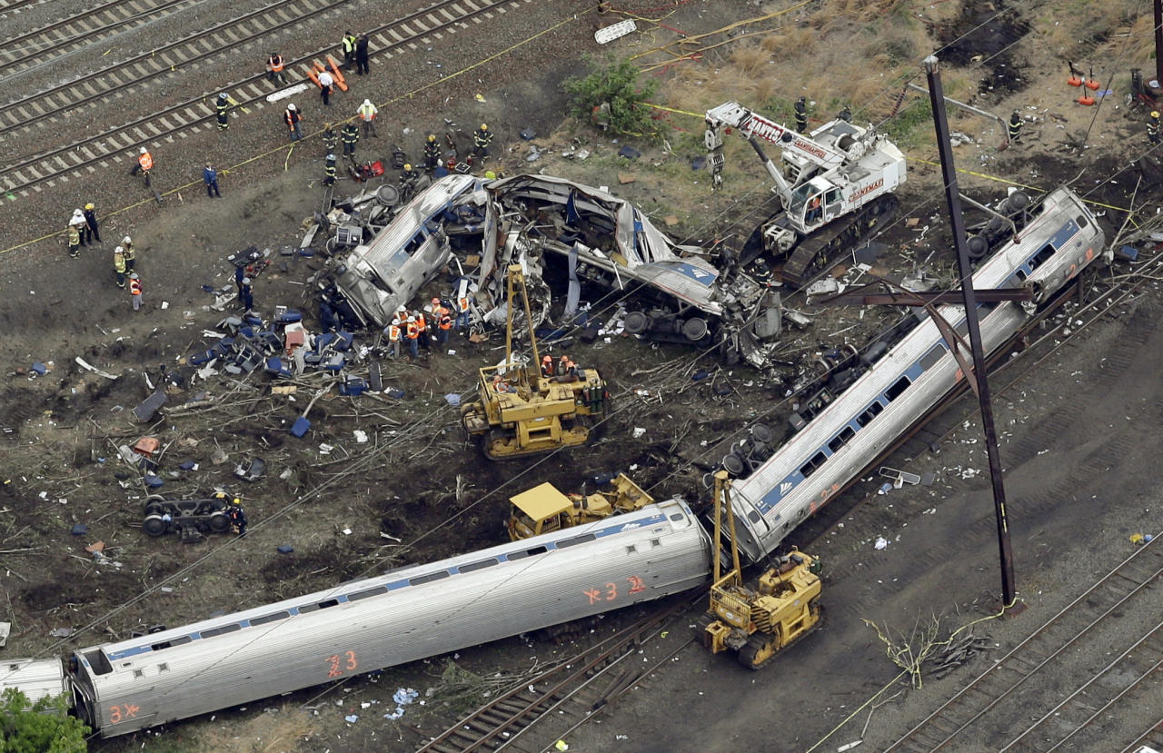 FILE- In this Wednesday, May 13, 2015, file photo, emergency personnel work at the scene of a derailment in Philadelphia of an Amtrak train headed to New York. Amtrak will pay about $265 million to settle claims related to a deadly derailment in Philadelphia that killed eight people and injured more than 200 others. Lawyers who negotiated the settlement said people will have their awards in hand by June instead of going through years of legal wrangling. (AP Photo/Patrick Semansky, File)