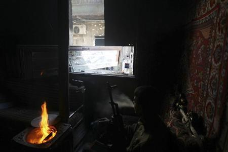 A Free Syrian Amy fighter rests in a damaged house in the Aghyol area of Aleppo