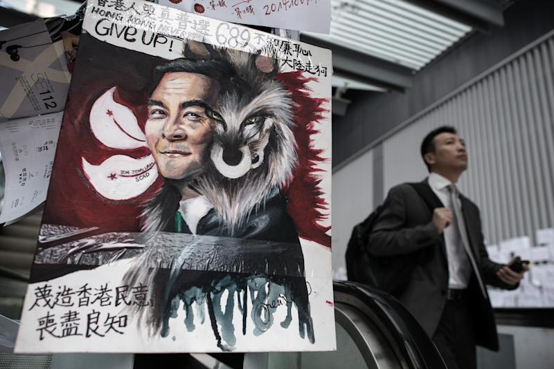 A man walks past artwork depicting Hong Kong chief executive Leung Chun-ying as a wolf, near the government headquarters in Hong Kong on October 10, 2014 (AFP Photo/Philippe Lopez)