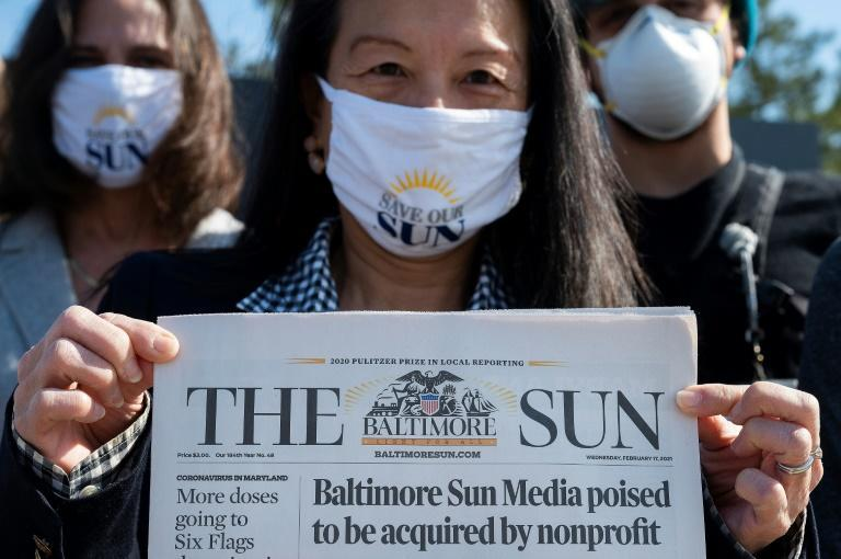 Baltimore Sun reporter Jean Marbella holds up the newspaper's front page that headlined its potential take over by a nonprofit group during an interview on March 11