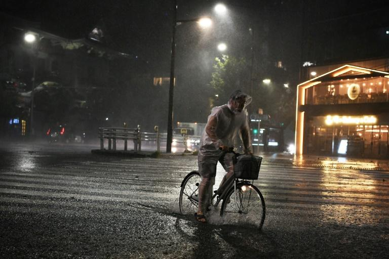 A man in Tokyo rides his bicycle during Typhoon Faxai, which made landfall just east of the Japanese capital