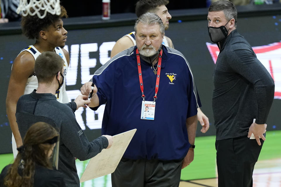West Virginia head coach Bob Huggins takes a marker and a white board during a timeout in the first half of a college basketball game against Morehead State in the first round of the NCAA tournament at Lucas Oil Stadium Friday, March 19, 2021, in Indianapolis. (AP Photo/Mark Humphrey)