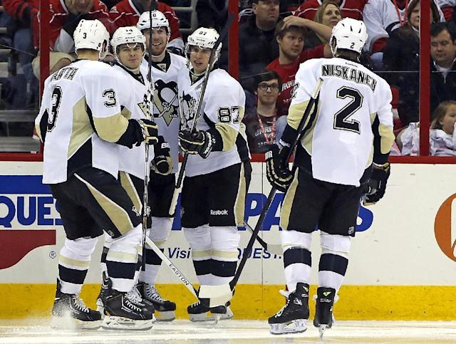 Pittsburgh Penguins' Sidney Crosby (87) celebrates his goal with teammates James Neal (18), Chris Kunitz (14), Olli Maatta (3), and Matt Niskanen (2) during the second period of an NHL hockey game against the Carolina Hurricanes, Friday, Dec. 27, 2013, in Raleigh, N.C. Pittsburgh won 4-3 in overtime. (AP Photo/Karl B DeBlaker)