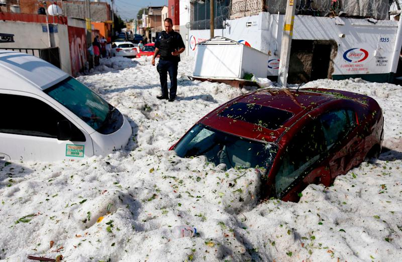 A policeman stands next to vehicles buried in hail in the eastern area of Guadalajara, Jalisco state, Mexico, on June 30, 2019.