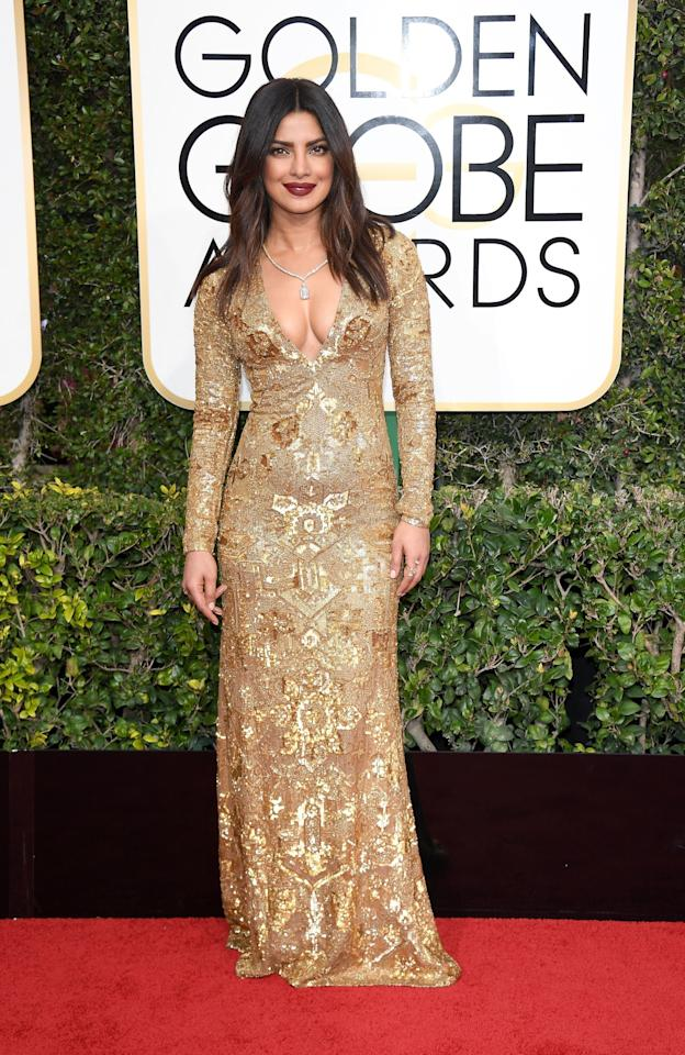 <p>Priyanka Chopra wore a one-of-a-kind hand-embroidered gold evening dress from Ralph Lauren Collection with sequins and glass beads that took 1,600 hours to make! (Photo: Getty Images) </p>