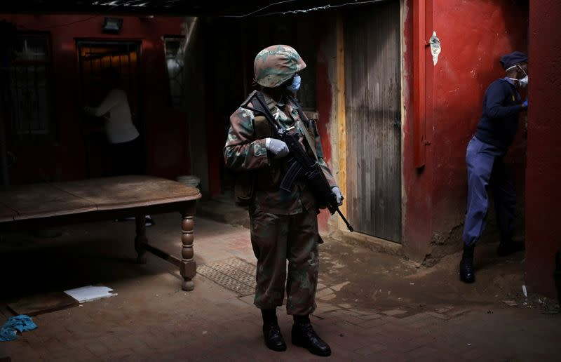 FILE PHOTO: A soldier and a member of the South African police service search a house
