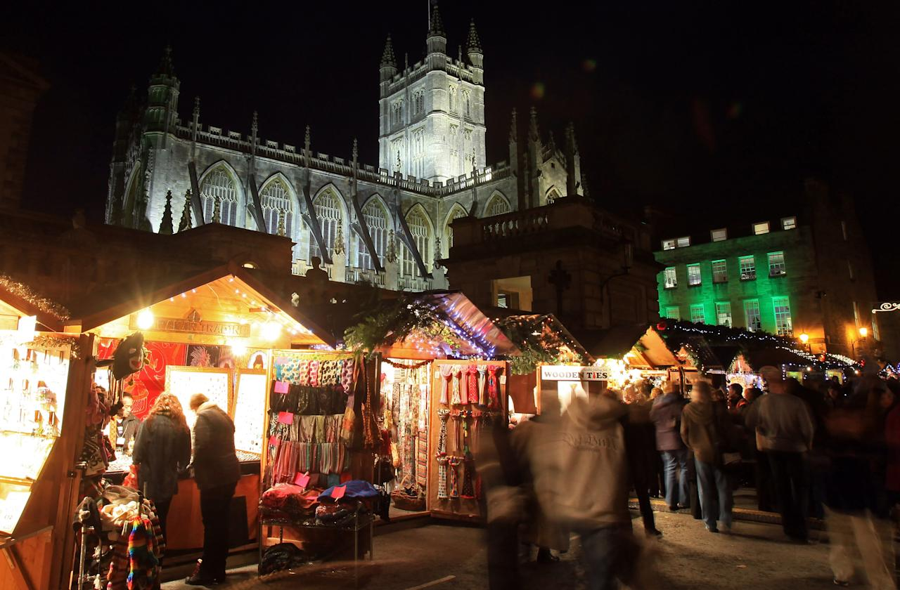 BATH, ENGLAND - NOVEMBER 24:  Christmas shoppers browse the offerings at the Bath Christmas Market on its opening night on November 24, 2011 in Bath, England. Originating in Germany, Christmas markets have become increasingly popular in British cities too, as a way of boosting festive retail sales and visitor numbers.  (Photo by Matt Cardy/Getty Images)