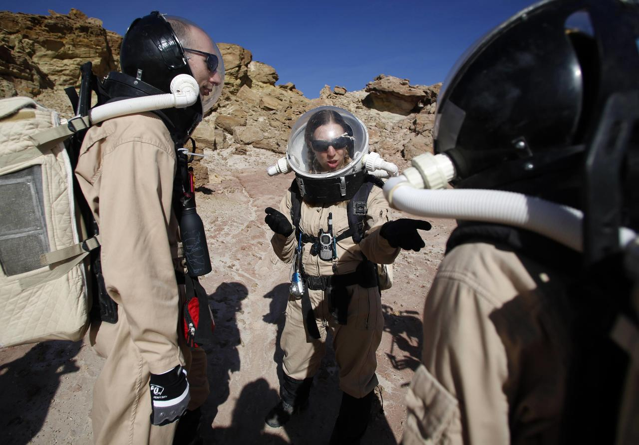 ðMelissa Battler (C), a geologist and commander of Crew 125 EuroMoonMars B mission, talks to members of the crew about collecting geologic samples for study at the Mars Desert Research Station (MDRS) in the Utah desert March 2, 2013. The MDRS aims to investigate the feasibility of a human exploration of Mars and uses the Utah desert's Mars-like terrain to simulate working conditions on the red planet. Scientists, students and enthusiasts work together developing field tactics and studying the terrain. All outdoor exploration is done wearing simulated spacesuits and carrying air supply packs and crews live together in a small communication base with limited amounts of electricity, food, oxygen and water. Everything needed to survive must be produced, fixed and replaced on site. Picture taken March 2, 2013. REUTERS/Jim Urquhart