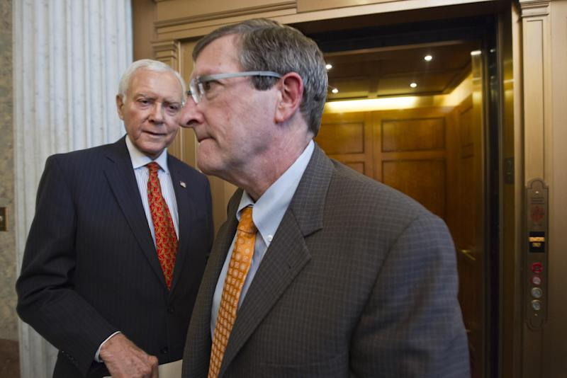 Sen. Orrin Hatch, R-Utah, left, and Sen. Kent Conrad, D-ND, right, both members of the tax-writing Senate Finance Committee, pass each other during final votes before the Senate leaves for a five-week recess, Thursday, Aug. 2, 2012, on Capitol Hill in Washington.  (AP Photo/J. Scott Applewhite)
