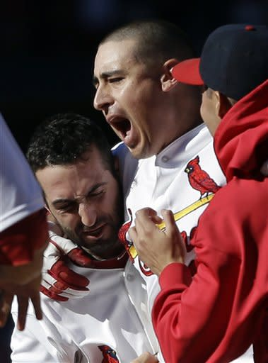 St. Louis Cardinals' Allen Craig, center, is congratulated by teammate Daniel Descalso, left, after hitting a game-winning single to score Matt Carpenter during the 10th inning of a baseball game against the Milwaukee Brewers, Sunday, Sept. 9, 2012, in St. Louis. (AP Photo/Jeff Roberson)